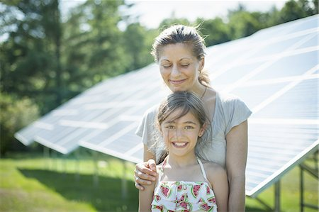 solar panel usa - A child and her mother in the fresh open air, beside solar panels on a sunny day at a farm in New York State, USA. Stock Photo - Premium Royalty-Free, Code: 6118-07351953