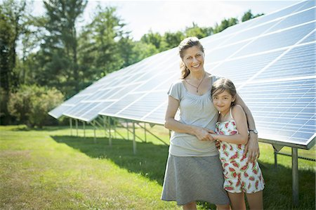 solar panel usa - A child and her mother in the fresh open air, beside solar panels on a sunny day at a farm in New York State, USA. Stock Photo - Premium Royalty-Free, Code: 6118-07351950