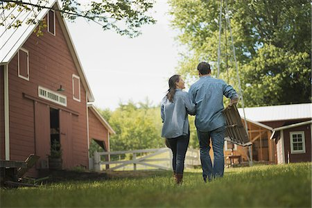 Two people, man and woman in the yard of a traditional farm in the USA. Stock Photo - Premium Royalty-Free, Code: 6118-07352011