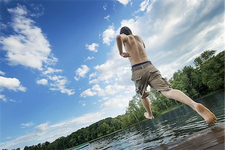 A boy taking a running jump into a calm pool of water, from a wooden jetty. Stock Photo - Premium Royalty-Free, Code: 6118-07352026