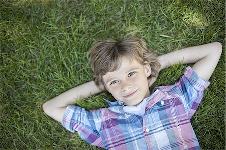 A boy lying on the grass, hands behind his head. Stock Photo - Premium Royalty-Free, Code: 6118-07352166