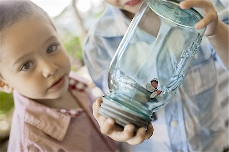 A child holding a glass jar and examining a butterfly. Stock Photo - Premium Royalty-Free, Code: 6118-07352170