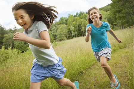 preteen asian girls - Two children, girls running and playing chase, laughing in the fresh air. Stock Photo - Premium Royalty-Free, Code: 6118-07352381