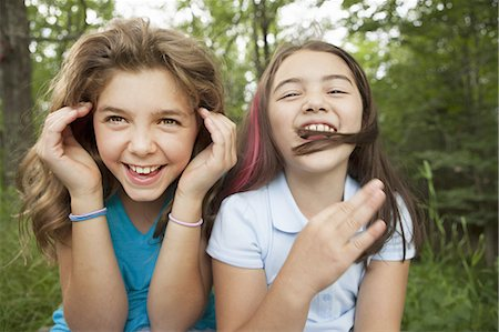 preteen asian girls - Two girls, friends sitting side by side, playing and laughing. Stock Photo - Premium Royalty-Free, Code: 6118-07352388