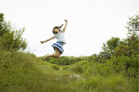 A young girl, leaping for joy, kicking up her heels in the air. Stock Photo - Premium Royalty-Free, Code: 6118-07352390