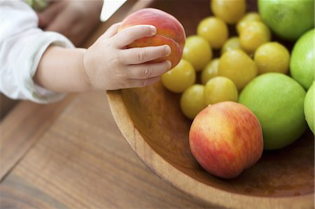 A small child, a one year old girl, grasping fruit from a bowl. Stock Photo - Premium Royalty-Free, Code: 6118-07352396