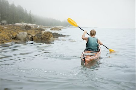 A man paddling a kayak on calm water in misty conditions. New York State, USA Stock Photo - Premium Royalty-Free, Code: 6118-07352420