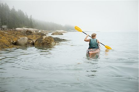 A man paddling a kayak on calm water in misty conditions. New York State, USA Stock Photo - Premium Royalty-Free, Code: 6118-07352424