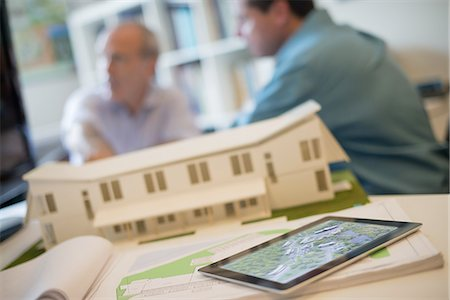 property release - Architects working on a green construction project, using computer technology, in an office. An architect's model of a house. Computer tablet. Stock Photo - Premium Royalty-Free, Code: 6118-07352603