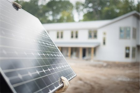 solar panel usa - A workman carrying a large solar panel at a green house construction site. Stock Photo - Premium Royalty-Free, Code: 6118-07352616