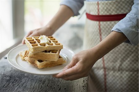 A woman holding a plate of fresh cooked waffles, with cream on top. Stock Photo - Premium Royalty-Free, Code: 6118-07352636
