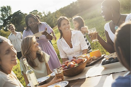 A family and friends having a meal outdoors.  A picnic or buffet in the early evening. Stock Photo - Premium Royalty-Free, Code: 6118-07352829