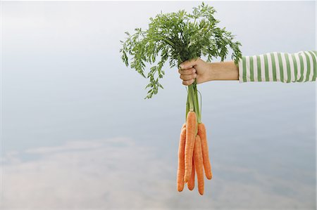 Nine year old girl holding organic carrots Stock Photo - Premium Royalty-Free, Code: 6118-07352837