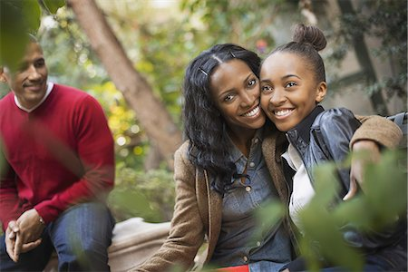 settlement - Scenes from urban life in New York City. Three people, two adults and a teenage girl. Mother and daughter hugging. Stock Photo - Premium Royalty-Free, Code: 6118-07353367
