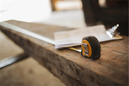 A reclaimed timber yard. Recycled plank of wood, measuring tape and a clipboard with paperwork. Stock Photo - Premium Royalty-Free, Code: 6118-07353394
