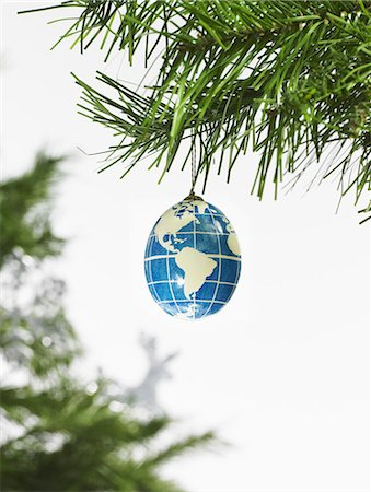 Still life. Green leaf foliage and decorations. A pine tree branch and a blue and white bauble. A globe with continents outlined on a blue background. Stock Photo - Premium Royalty-Free, Code: 6118-07353494