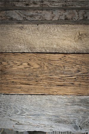 A heap of recycled reclaimed timber planks of wood. Environmentally responsible reclamation in a timber yard. Varieties of wood, with grain and colour details. Stock Photo - Premium Royalty-Free, Code: 6118-07353403