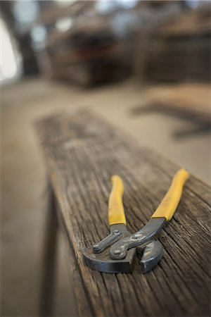 A heap of recycled reclaimed timber planks of wood. Environmentally responsible reclamation in a timber yard. A pair of pliers on a plank of wood. Stock Photo - Premium Royalty-Free, Code: 6118-07353401
