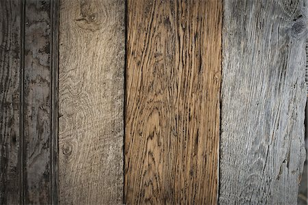 A heap of recycled reclaimed timber planks of wood. Environmentally responsible reclamation in a timber yard. Varieties of wood, with grain and colour details. Stock Photo - Premium Royalty-Free, Code: 6118-07353402