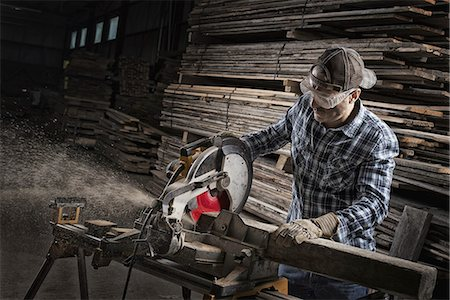 piles of work - A reclaimed lumber workshop. A man in protective eye goggles using a circular saw to cut timber. Stock Photo - Premium Royalty-Free, Code: 6118-07353420