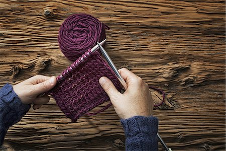 A woman holding two knitting needles, and a piece of knitting, in purple wool. Stock Photo - Premium Royalty-Free, Code: 6118-07353436