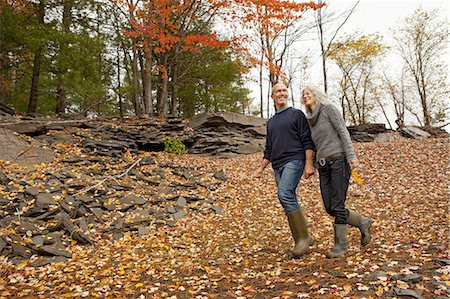A couple, man and woman on a day out in autumn walking through fallen leaves. Holding hands. Stock Photo - Premium Royalty-Free, Code: 6118-07353557