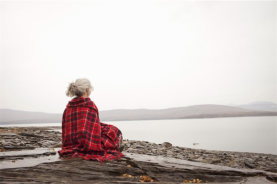 A woman looking out over the water on the shores of a calm lake, wrapped in a tartan rug. Stock Photo - Premium Royalty-Free, Image code: 6118-07353560