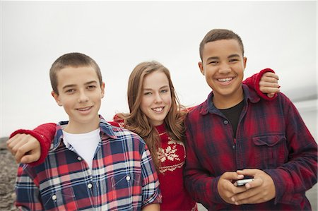 A day out at Ashokan lake. Three teenagers, boys and a girl in a row. Friends. Stock Photo - Premium Royalty-Free, Code: 6118-07353576