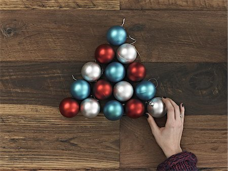 A collection of blue, red and silver ornaments arranged in a triangular shape on a wooden board. A Christmas tree shape. A person's hand placing the final ball. Stock Photo - Premium Royalty-Free, Code: 6118-07353503
