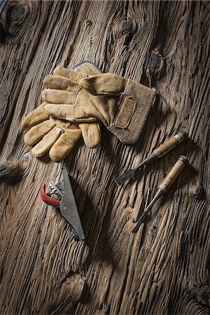 A reclaimed lumber yard workshop. A pair of leather working gloves, and handheld traditional tools. Stock Photo - Premium Royalty-Free, Code: 6118-07353641