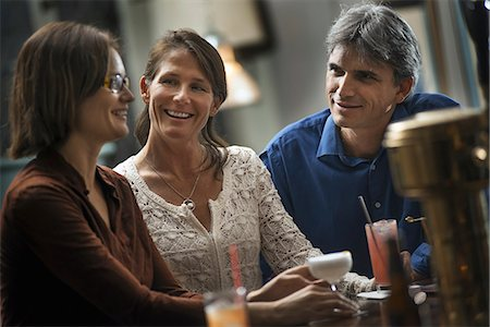exterior bar - Three people meeting for a drink.  Two women and a man sitting at a bar. Friends socialising. Stock Photo - Premium Royalty-Free, Code: 6118-07353647