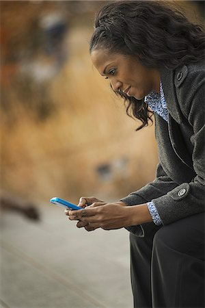 settlement - City life. A woman in a coat, checking and texting, keeping in contact, using a mobile phone. Stock Photo - Premium Royalty-Free, Code: 6118-07353685