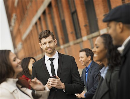 expressive - City life. A group of people on the go, keeping in contact, using mobile phones, and talking to each other. Men and women, professionals in a group. Stock Photo - Premium Royalty-Free, Code: 6118-07353689
