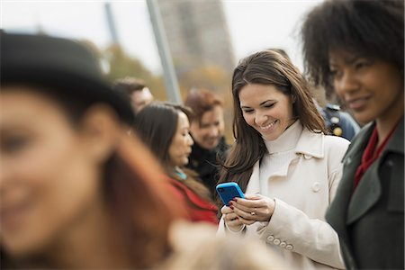 settlement - City life. A group of people on the go, keeping in contact, using mobile phones, and talking to each other. A crowd of women. Stock Photo - Premium Royalty-Free, Code: 6118-07353696