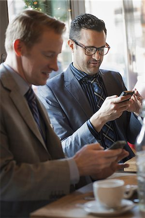 Business people in the city. Two men sitting at a cafe table checking their mobile phone messages and keeping in touch. Stock Photo - Premium Royalty-Free, Code: 6118-07353634