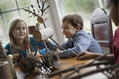 Three children sitting at a table in family home. A twig reindeer in the centre, with branches and twigs to make objects. Stock Photo - Premium Royalty-Free, Code: 6118-07353749