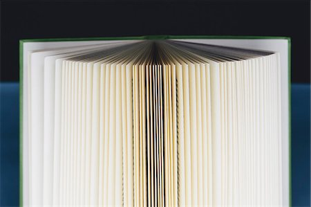 page - A hard cover printed book, opened and upright. Pages fanned out with graduated yellowing edges, changing to brown and black in the centre. Stock Photo - Premium Royalty-Free, Code: 6118-07354058