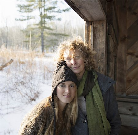 Two people, a mother and daughter, side by side, in the porch of a wooden barn on a farm. A winter's day. Stock Photo - Premium Royalty-Free, Code: 6118-07354076