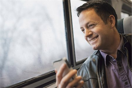 A mature man sitting at a window seat on a train, holding his mobile phone. Smiling and looking in the distance. Stock Photo - Premium Royalty-Free, Code: 6118-07354152