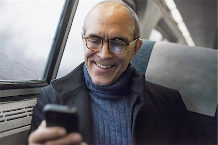 A mature man sitting by a window in a train carriage, using his mobile phone, keeping in touch on the move. Stock Photo - Premium Royalty-Free, Code: 6118-07354154