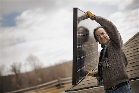 A man carrying a large solar panel across a farmyard. Stock Photo - Premium Royalty-Free, Code: 6118-07354193