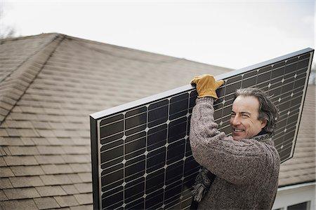 solar power - A man carrying a large solar panel across a farmyard. Stock Photo - Premium Royalty-Free, Code: 6118-07354194