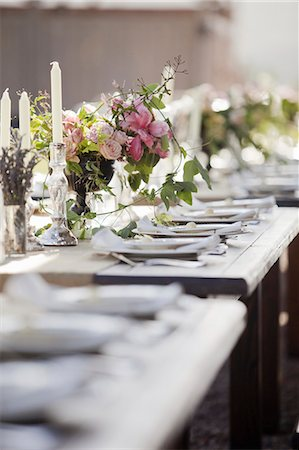 A formal wedding breakfast table, laid for a feast. Fresh flowers in the centre. Stock Photo - Premium Royalty-Free, Code: 6118-07354128