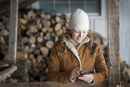 An organic farm in upstate New York, in winter. A woman in sheepskin coat and woollen hat using a cell phone. Stock Photo - Premium Royalty-Free, Code: 6118-07354291