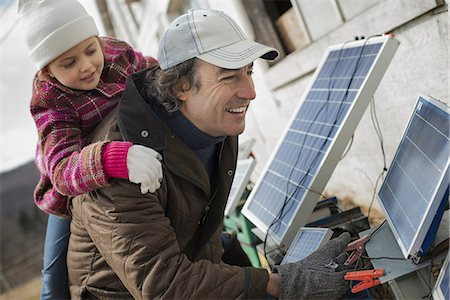 solar panel usa - A man giving a child a piggybank while trying to connect the leads for solar power panels. Stock Photo - Premium Royalty-Free, Code: 6118-07354205