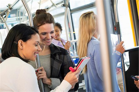 New York City park. People, men and women on a city bus. Public transport. Two women looking at a handheld digital tablet. Stock Photo - Premium Royalty-Free, Code: 6118-07354343