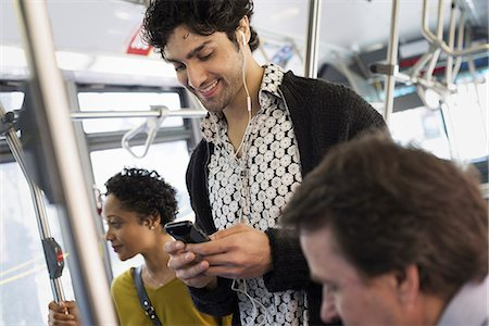 New York City park. People, men and women on a city bus. Public transport. Keeping in touch. A young man checking his cell phone. Stock Photo - Premium Royalty-Free, Code: 6118-07354340