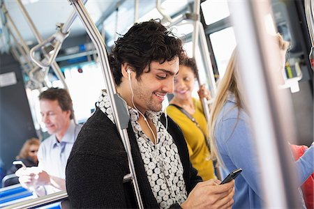 New York City park. People, men and women on a city bus. Public transport. Keeping in touch. A young man checking his cell phone. Stock Photo - Premium Royalty-Free, Code: 6118-07354341
