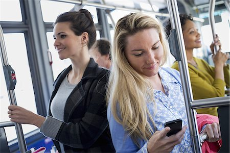 New York City park. People, men and women on a city bus. Public transport. Keeping in touch. A young woman checking or using her cell phone. Stock Photo - Premium Royalty-Free, Code: 6118-07354342