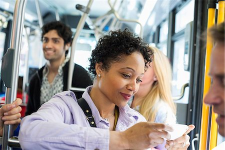 New York City park. People, men and women on a city bus. Public transport. Keeping in touch. A young woman checking or using her cell phone. Stock Photo - Premium Royalty-Free, Code: 6118-07354347